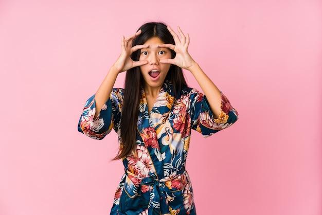 Die junge asiatische frau, die pyjamas eines kimonos hält augen trägt, öffnete sich, um eine erfolgschance zu finden.