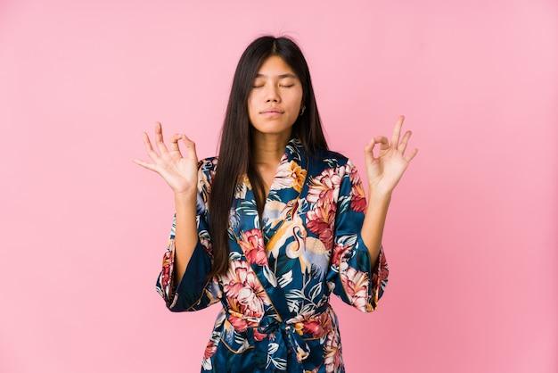 Die junge asiatische frau, die pyjamas eines kimonos trägt, entspannt sich nach hartem arbeitstag, sie führt yoga durch.