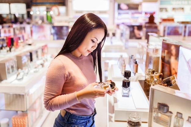 Die junge asiatische frau, die zutrifft und beschließen, parfüm im zollfreien speicher am internationalen flughafen zu kaufen