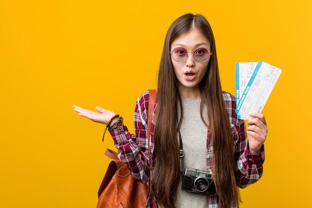 Die junge asiatische frau, halten flugtickets beeindruckt, kopienraum auf palme halten.