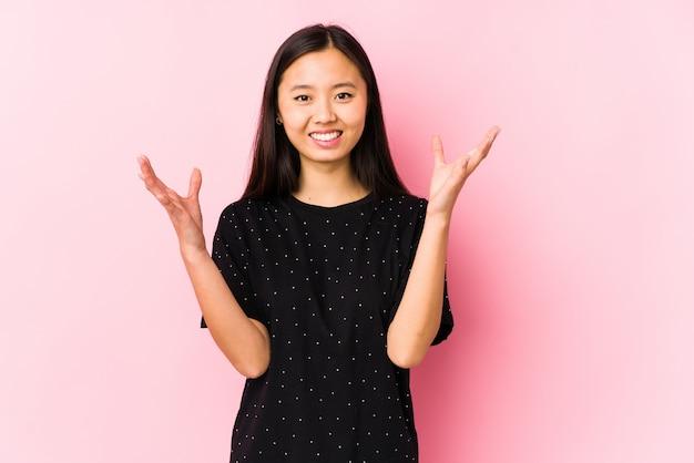 Die junge asiatische frau, welche die elegante kleidung trägt, lokalisierte das empfangen einer angenehmen überraschung, aufgeregt und hände anhebend.