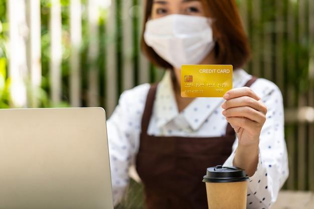 Die junge asiatische geschäftsfrau besitzt ein café mit einem tablet und einer kreditkarte, um den kunden zu sagen, dass sie für den gesamten service bar bezahlen sollen