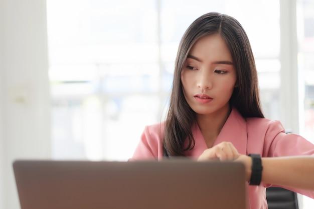Die junge asiatische geschäftsfrau, welche die zeit überprüft, arbeiten mit laptop-computer.