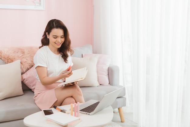 Die junge asiatische online-geschäftsinhaberin überprüft ihr produkt in ihrer bürowerkstatt.