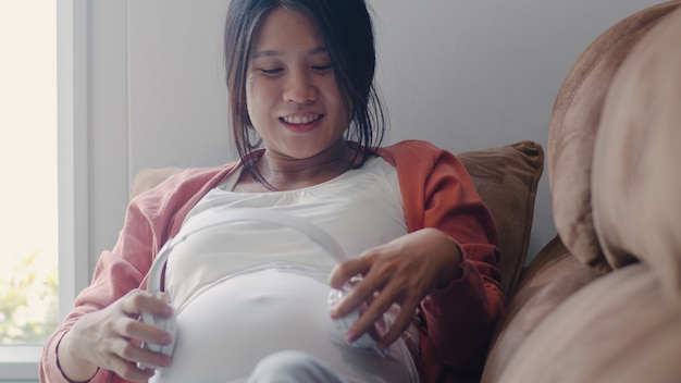 Die junge asiatische schwangere frau, die telefon und kopfhörer verwendet, spielen musik für baby im bauch. die mutter, die glücklich sich fühlt, positiv und ruhig lächelnd, während mach s gut das kind, das zu hause auf sofa im wohnzimmer liegt.