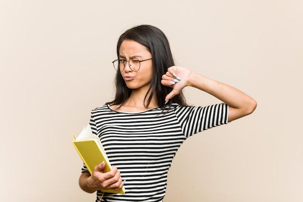 Die junge asiatische studentin, die ein buch hält, fühlt sich stolz und selbstbewusst, beispiel zu folgen.