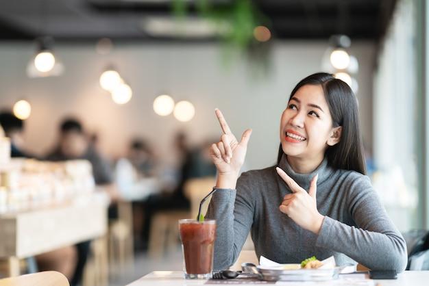 Die junge attraktive asiatische frau, die oben zeigt, und schauen zur seite