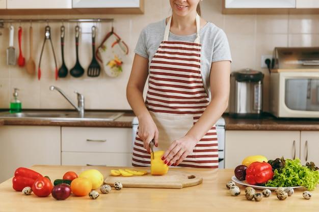 Die junge attraktive frau in einer schürze schneidet mit einem messer in der küche gemüse für salat. diätkonzept. gesunder lebensstil. kochen zu hause. essen zubereiten.