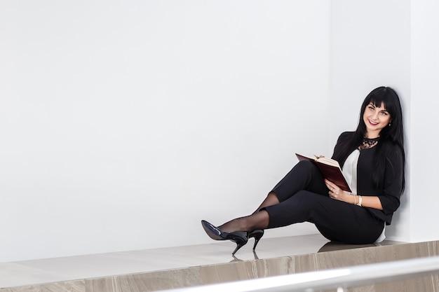 Die junge attraktive glückliche brunettefrau, die ein notizbuch hält, kleidete in einem schwarzen anzug an, der auf einem boden in einem büro sitzt und lächelte.