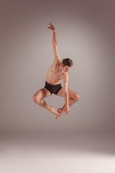 Die junge attraktive moderne balletttänzerin springt über grauen hintergrund