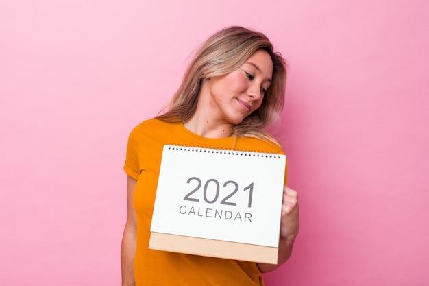 Die junge australische frau, die einen auf rosa hintergrund isolierten kalender hält, sieht beiseite lächelnd, fröhlich und angenehm aus.