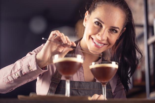 Die junge bardame lächelt, nachdem sie zwei espresso-martini-kurzgetränke mit einem kaffee zubereitet hat.