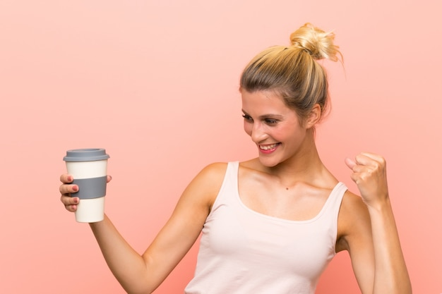 Die junge blonde frau, die ein hält, nehmen den kaffee weg, der einen sieg feiert