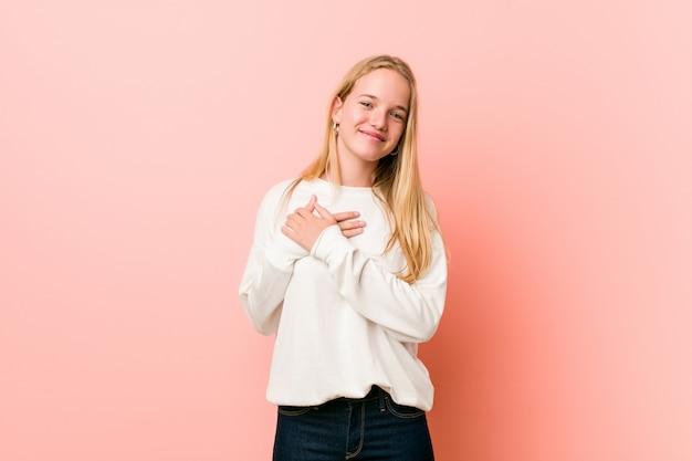 Die junge blonde teenagerfrau hat einen freundlichen ausdruck und drückt die handfläche auf die brust. liebeskonzept.