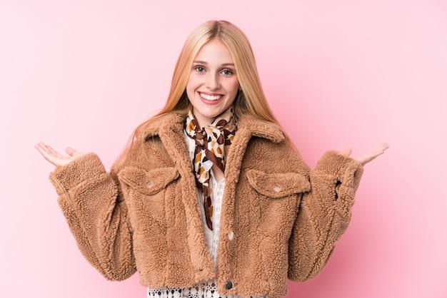 Die junge blondine, die einen mantel gegen eine rosa wand tragen, machen skala mit den armen, fühlen sich glücklich und überzeugt.