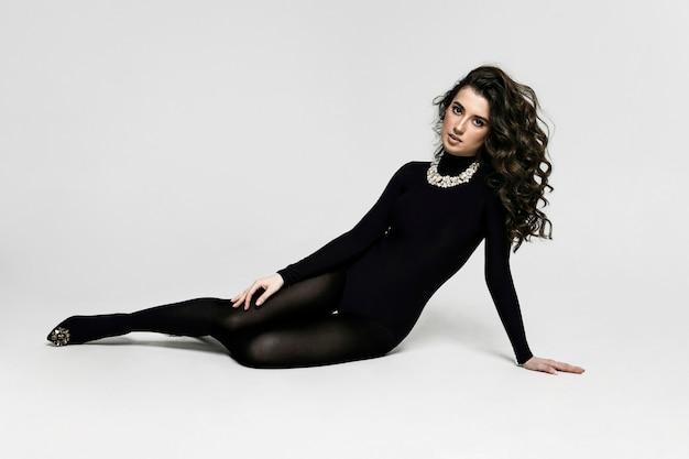 Die junge brünette lockige frau in schwarzem body und high heel liegt auf dem boden. sie hat einen gesunden, schlanken und athletischen körper. bild in voller länge.