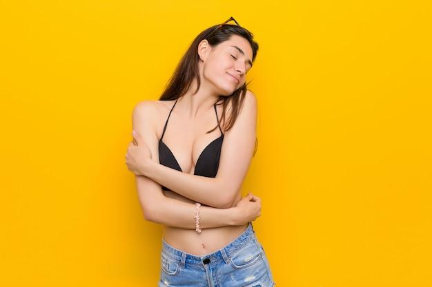 Die junge brunettefrau, die einen bikini trägt, umarmt, lächelt sorglos und glücklich.