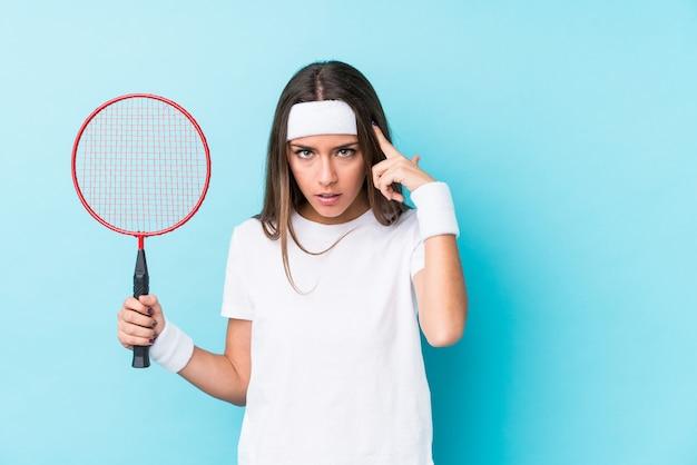 Die junge caucasic frau, die badminton spielt, lokalisierte das zeigen des tempels mit dem finger und dachte, konzentrierte sich auf eine aufgabe.