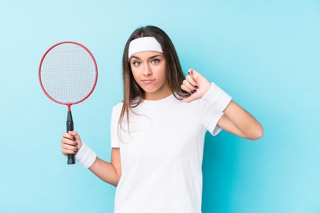 Die junge caucasic frau, die badminton spielt, lokalisierte das zeigen einer abneigungsgeste, daumen unten. uneinigkeit konzept.