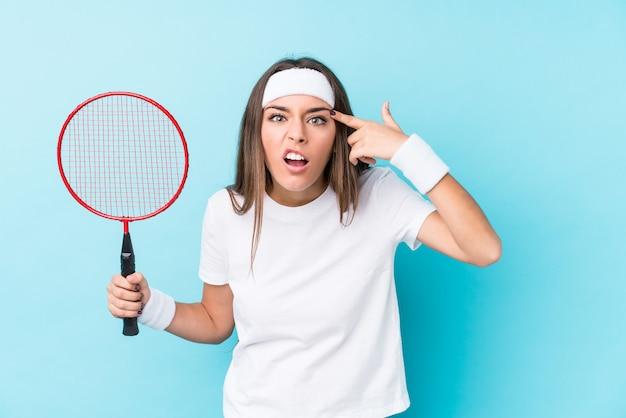 Die junge caucasic frau, die badminton spielt, lokalisierte das zeigen einer enttäuschungsgeste mit dem zeigefinger.