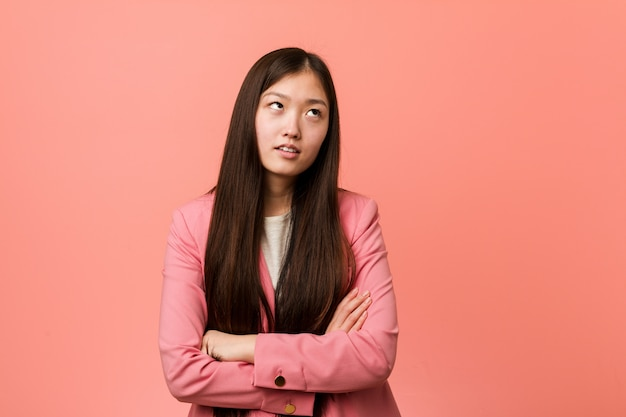 Die junge chinesische frau des geschäfts, die den rosa anzug trägt, ermüdete von einer sich wiederholenden aufgabe.