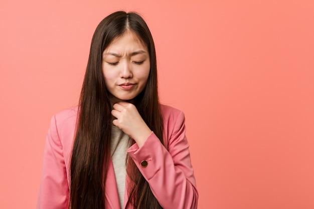 Die junge chinesische frau des geschäfts, die rosa anzug trägt, leidet die schmerz in der kehle wegen eines virus oder einer infektion.