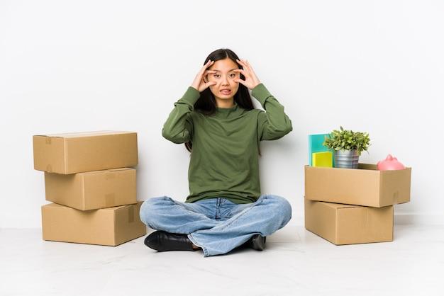 Die junge chinesische frau, die auf ein neues zuhause umzieht, das augen hält, öffnete sich, um eine erfolgschance zu finden.