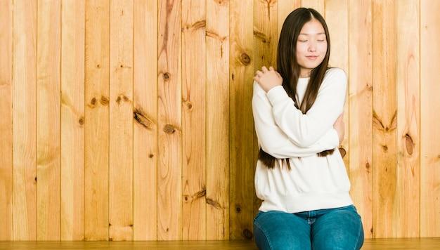 Die junge chinesische frau, die auf einem hölzernen platz sitzt, umarmt und lächelt sorglos und glücklich.