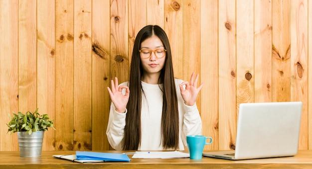 Die junge chinesische frau, die auf ihrem schreibtisch studiert, entspannt sich nach hartem arbeitstag, sie führt yoga durch.