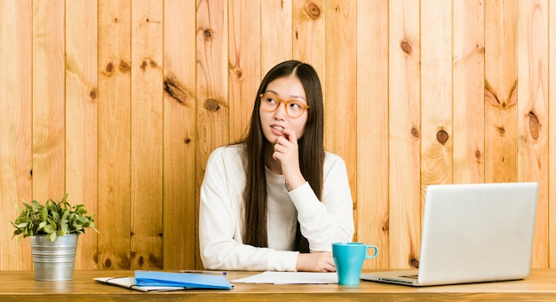 Die junge chinesische frau, die auf ihrem schreibtisch studiert, entspannte sich das denken an etwas, das einen kopienraum betrachtet.