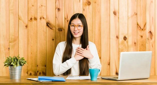 Die junge chinesische frau, die auf ihrem schreibtisch studiert, hat den freundlichen ausdruck und drückt palme zur brust. liebes-konzept.