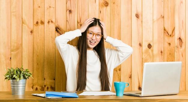 Die junge chinesische frau, die auf ihrem schreibtisch studiert, lacht, hände auf kopf froh halten.