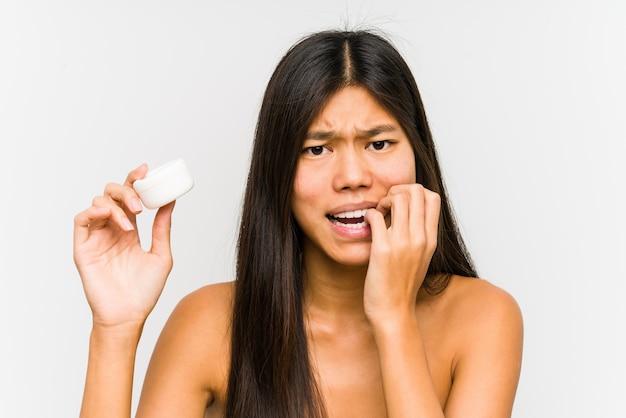 Die junge chinesische frau, die eine feuchtigkeitscreme hält, lokalisierte die beißenden fingernägel, nervös und sehr besorgt.