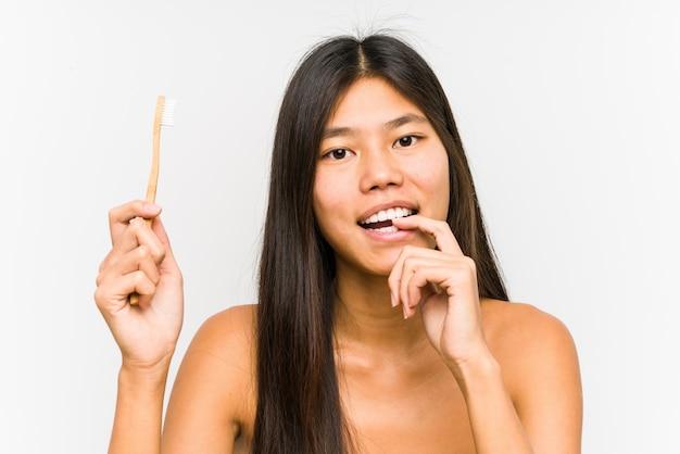 Die junge chinesische frau, die eine zahnbürste hält, lokalisierte das entspannte denken an etwas, das einen kopienraum betrachtet.