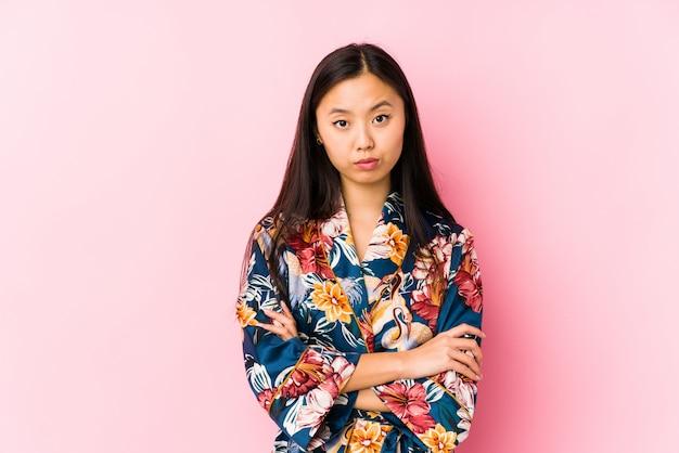 Die junge chinesische frau, die einen kimono-pyjama trägt, lokalisierte das unglückliche schauen mit sarkastischem ausdruck.