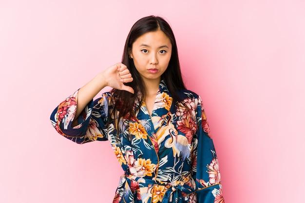 Die junge chinesische frau, die einen kimonopyjama trägt, lokalisierte das zeigen einer abneigungsgeste, daumen unten. uneinigkeit konzept.