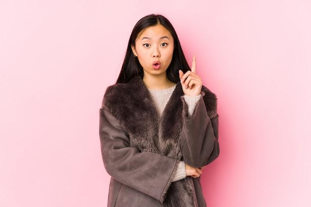 Die junge chinesische frau, die einen mantel trägt, lokalisierte das haben irgendeiner großartigen idee, konzept der kreativität.