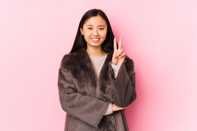 Die junge chinesische frau, die einen mantel trägt, lokalisierte das zeigen des nummer zwei mit den fingern.