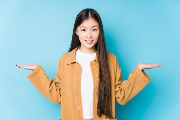 Die junge chinesische frau, die in einer blauen wand lokalisiert aufwirft, macht skala mit den armen, fühlt sich glücklich und überzeugt.