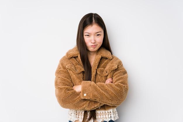 Die junge chinesische frau, die in einer weißen wand aufwirft, isolierte stirnrunzelndes gesicht in missfallen, hält arme verschränkt.