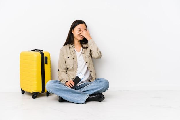 Die junge chinesische reisendfrau, die eine bordkarte halten sitzt, blinken durch verlegenes bedeckungsgesicht der finger an.