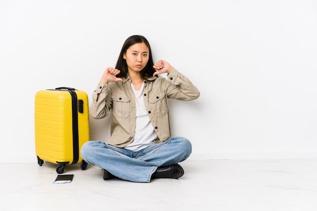Die junge chinesische reisendfrau, die eine bordkarte halten sitzt, fühlt sich stolz und selbstbewusst, beispiel zu folgen.
