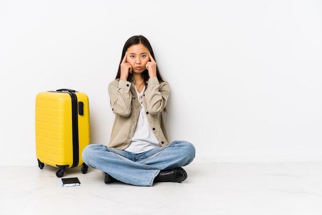 Die junge chinesische reisendfrau, die eine bordkarte halten sitzt, konzentrierte sich auf eine aufgabe und hielt die zeigefinger, die kopf zeigen.