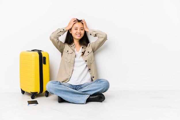Die junge chinesische reisendfrau, die eine bordkarte halten sitzt, lacht, hände auf kopf froh halten