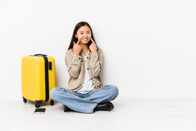 Die junge chinesische reisendfrau, die eine bordkarte halten sitzt, lächelt und zeigt finger auf mund.