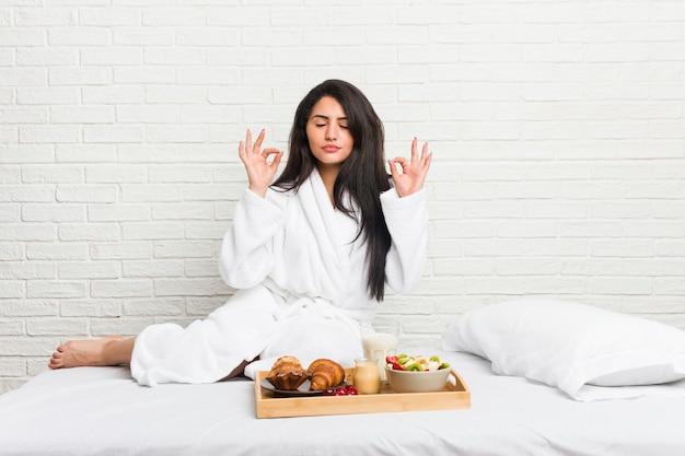 Die junge curvy frau, die ein frühstück auf dem bett nimmt, entspannt sich nach hartem arbeitstag, sie führt yoga durch.