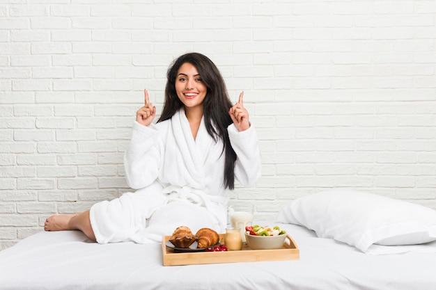 Die junge curvy frau, die ein frühstück auf dem bett nimmt, zeigt mit beiden vorderen fingern an, die sich eine leerstelle zeigen.