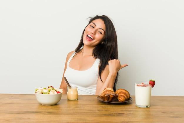 Die junge curvy frau, die ein frühstück nimmt, zeigt mit dem daumenfinger weg, lacht und sorglos.