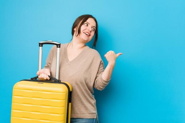 Die junge curvy frau, die einen koffer hält, zeigt mit dem daumenfinger weg, lacht und sorglos.