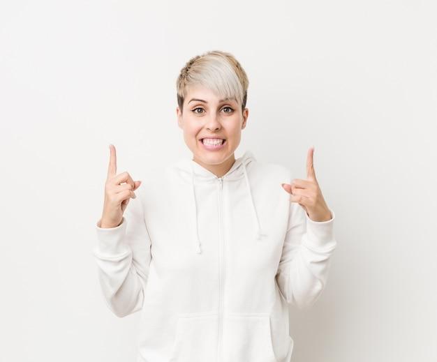 Die junge curvy frau, die einen weißen hoodie trägt, zeigt mit beiden vorderen fingern an, die sich eine leerstelle zeigen.